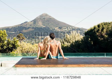 Rear view of couple sitting bu the pool looking at the landscape