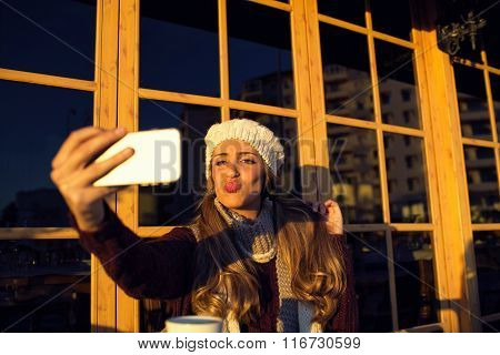 Young woman making selfie on her phone throwing a kiss out while sitting in cafe outdoors