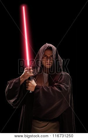 Vertical shot of a male warrior with red laser sword on black background