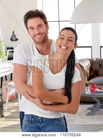 Happy loving couple embracing at home, laughing, looking at camera.