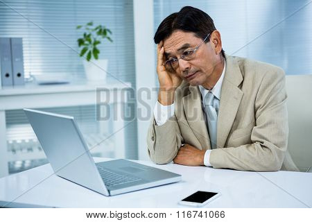 Undecided businessman looks his computer in his office