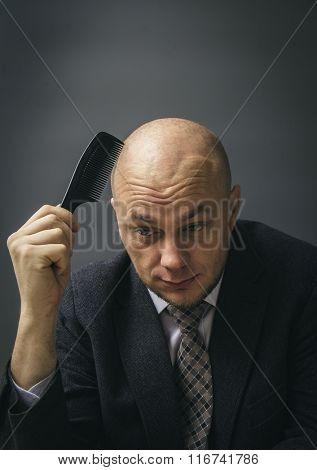 Bald businessman combing his nonexistent hair