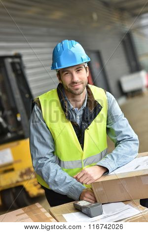 Portrait of warehouseman scanning merchandise on dock