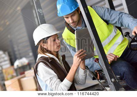 Warehouseman driving cart, listening to operator instructions