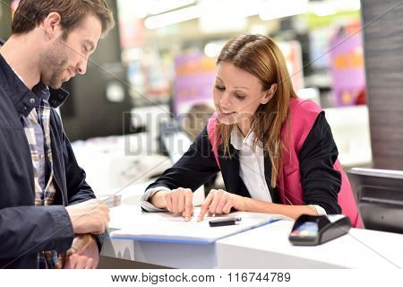 Car rental assistant giving information to customer
