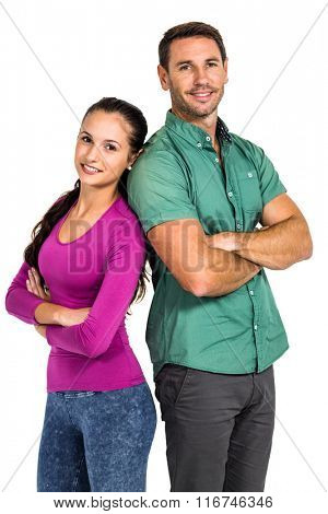 Smiling couple standing back to back with arms crossed looking at the camera on white screen