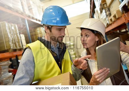 Store manager with warehouseman checking stock levels