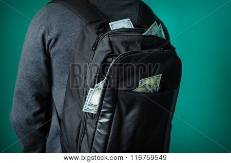 Man With A Black Backpack From Which Protrude Dollars