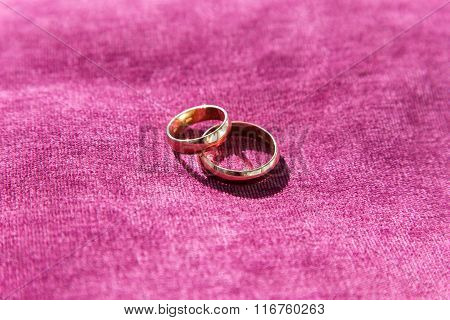 Two Golden Wedding Rings On Purple Brocade