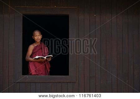 BAGAN, MYANMAR - DEC 11, 2015: Unidentified Buddhism neophyte read a book in Buddihist temple on December 11, 2015 in Bagan, Myanmar. Southeast Asian neophyte reading a book in a Buddihist temple