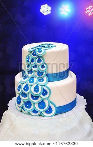 Beautiful White Three-tiered Cake On A Blue Background