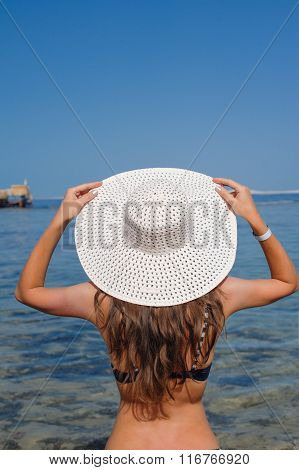 Happy woman with hat enjoying beach relaxing in summer by tropical blue water