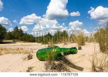 Abandoned green glass bottle in sands