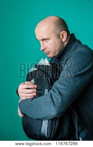greedy man holding a black bag of money