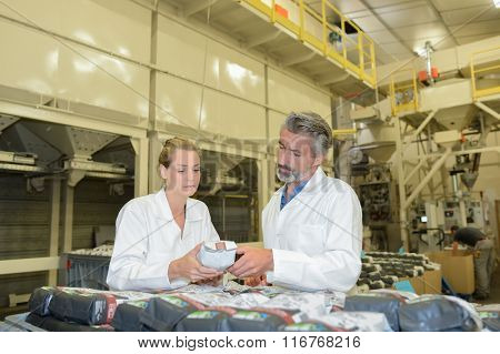 Man and woman inspecting packets in factory