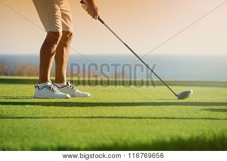 Golfer is going to tee off at sunset