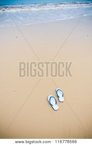 White Sandals With Blue Stripe Left On Beach.