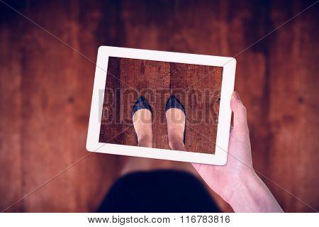 Feminine hand holding tablet against weathered oak floor boards background