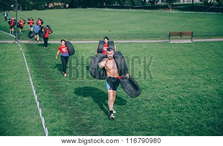 Runners carrying tires in a test of extreme obstacle race