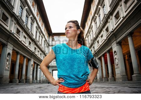 Now it is time to invest in your body and no matter you are at hometown or traveling. Fitness young sporty woman in sportswear and mp3 player staying in front of Uffizi gallery in Florence Italy poster
