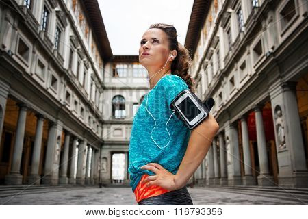 Now it is time to invest in your body and no matter you are at hometown or traveling. Young sporty female with headset staying in front of Uffizi gallery and listening music poster