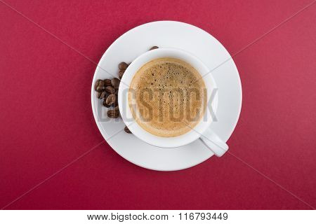 Coffee cup and beans on a red background