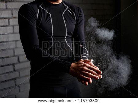 Closeup young man applying chalk powder