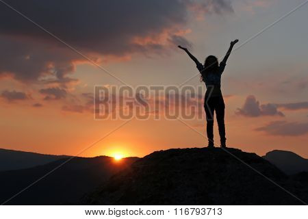 Silhouette Of A Girl Standing On A Mountain With His Hands Up Against The Setting Sun. Girl Standing