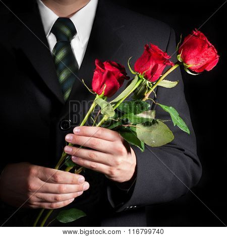 Man holding red roses. Valentine's day concept.