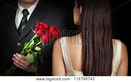 Young couple in love. Man gives his girlfriend red roses.