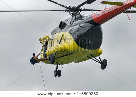 Rescuer is landed from MI-8 helicopter by rope