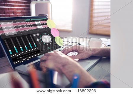 Music app against cropped image of graphic designer working on laptop