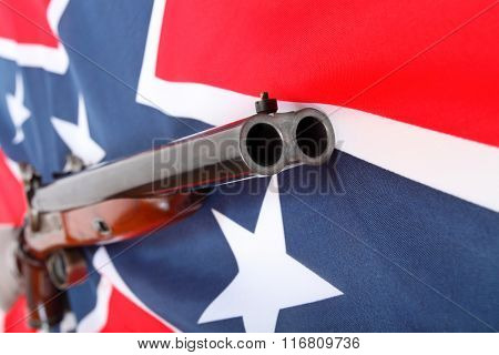 Confederate style cavalry percussion shotgun on confederate flag. Confederate guerrilla using this weapon during the American Civil War. Closeup with shallow DOF.