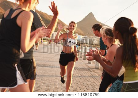 Group of spectators cheering runners just before the finish line. Female runner finishing the race with her team applauding her efforts. poster
