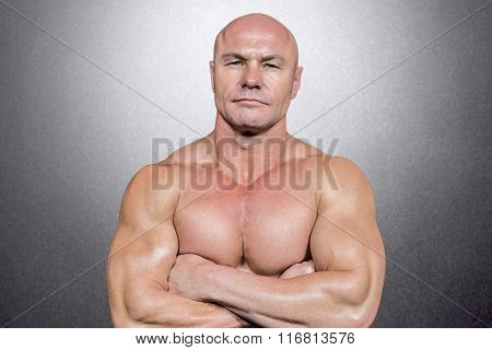 Portrait of man with arms crossed against grey