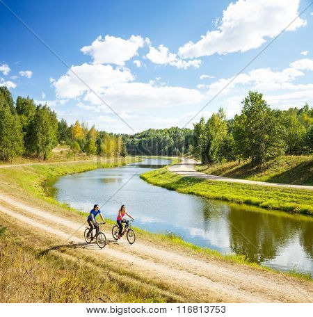 Young Happy Couple Riding Bicycles by the River
