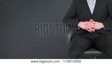 Stern businessman sitting on an office chair against grey background