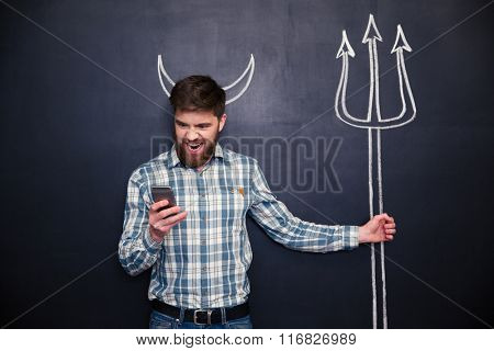 Handsome bearded young man playing role of devil standing over blackboard background with drawn horns and trident