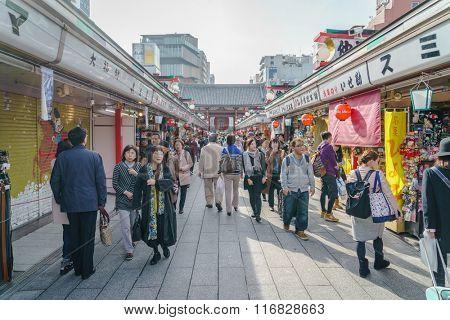 TOKYO,JAPAN - 24 November  2015 :Tourists walk on Nakamise Dori in Sensoji shrine.Sensoji temple with a variety of traditional, local snacks and tourist souvenirs for centuries.