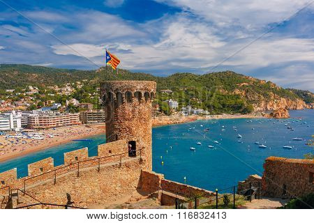 Round tower with the flag of Catalonia in fortress, Gran Platja beach and Badia de Tossa bay in Tossa de Mar on Costa Brava, Catalunya, Spain poster