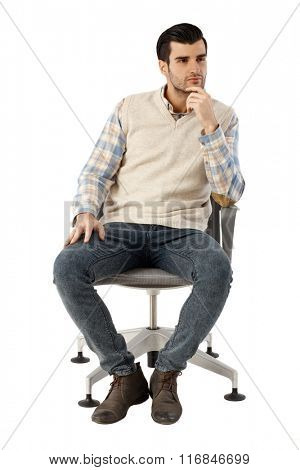 Young man thinking in swivel chair over white background.