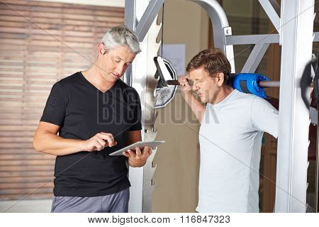 Senior man weightlifting barbell with personal trainer holding tablet computer