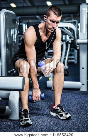 Muscular man with headphones lifting dumbbells at gym