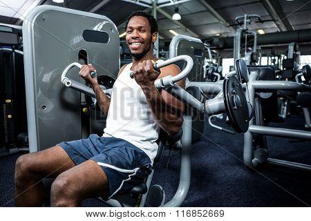 Smiling muscular man using exercise machine at gym