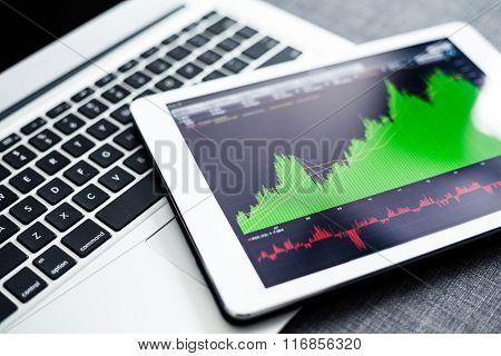 Stock market graphs on tablet pc with laptop computer