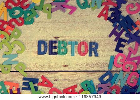 Debtor Word Block Concept Photo On Plank Wood