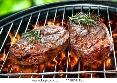 Grilled beef steaks over the coals on a barbecue grill
