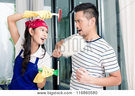 Asian woman and man having fun cleaning home staging a mock fight with chores utensils