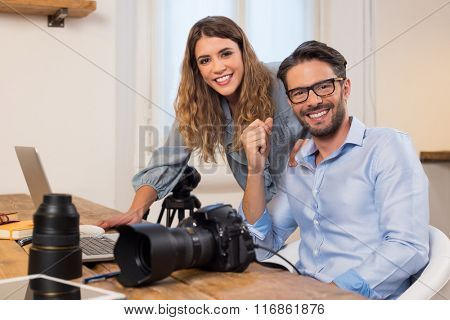 Professional photographers with camera and laptop computer working at studio. Photographer with assistant sitting in office and looking at camera. Team of photographers working together.
