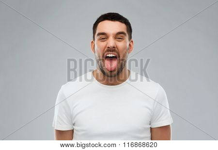 man showing his tongue over gray background